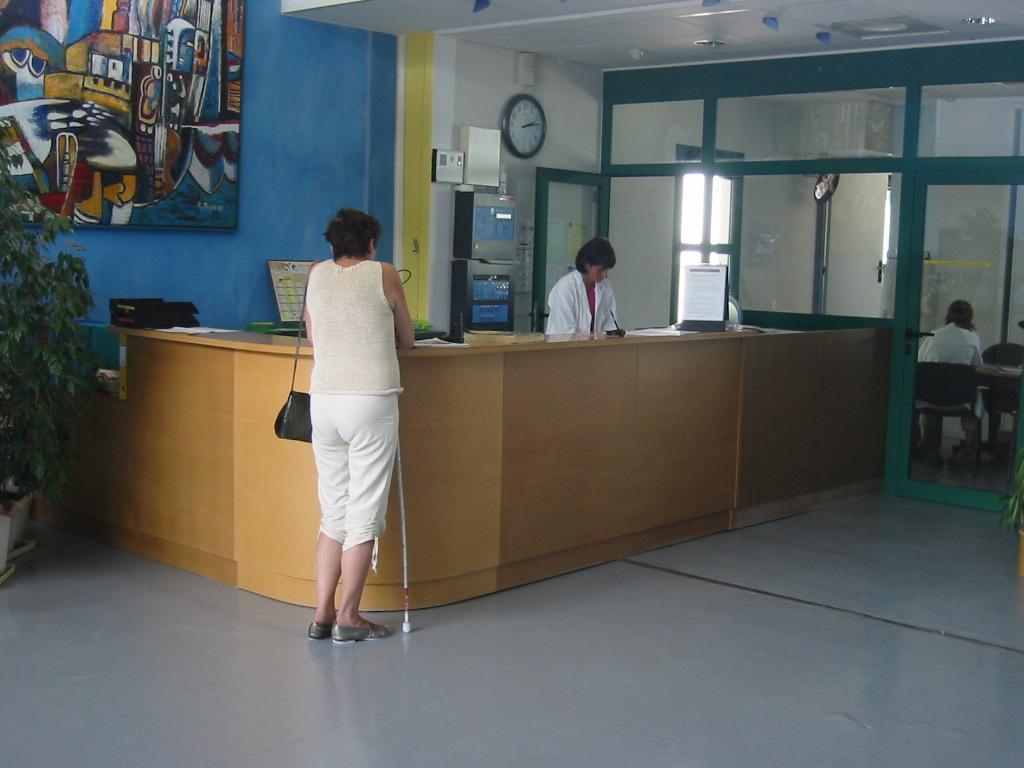 Photo d'une personne munie d'une canne longue face au comptoir d'accueil