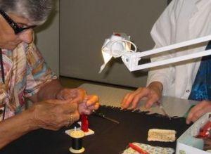 Femme utilisant un enfile aiguille éclairé par une lampe