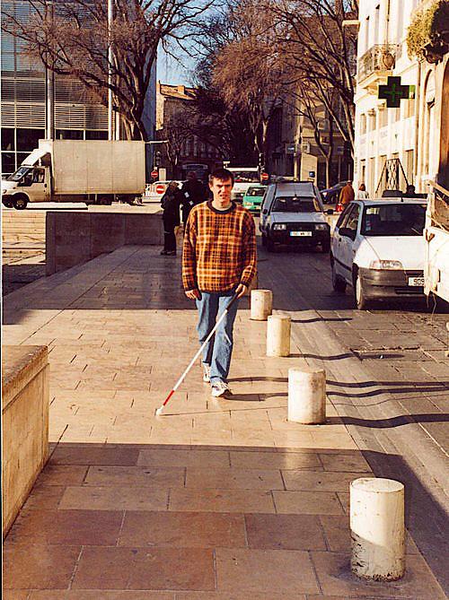 Homme muni d'une canne longue marchant sur un trottoir en centre ville