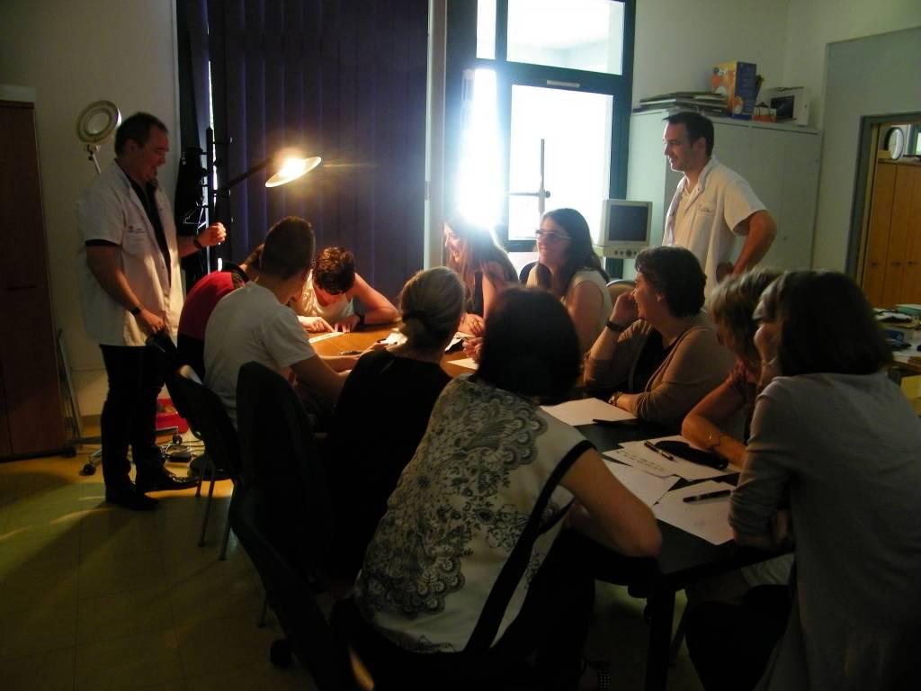 Groupe d'étudiants assis autour d'une table encadrés par deux formateurs debout