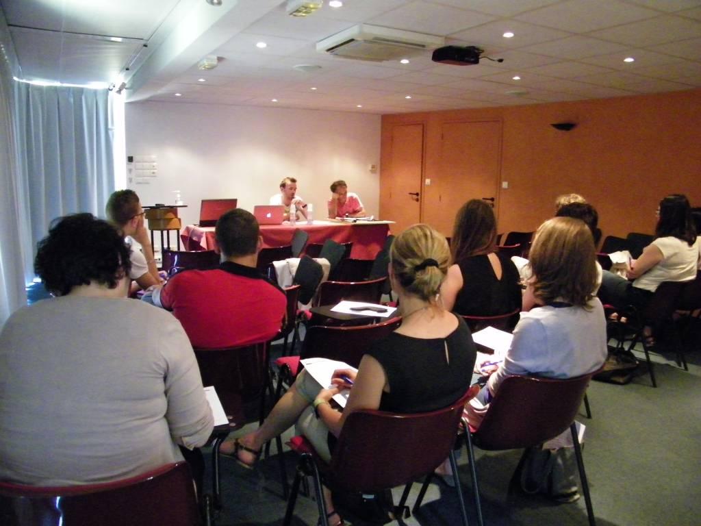 Groupe d'étudiants en salle de conférence face à deux formateurs