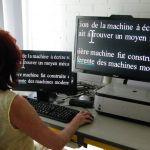 Femme assise devant un petit écran et un grand écran d'ordinateur lisant un texte en gros caractères