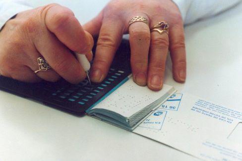 Écriture en braille sur un talon de chèque avec une tablette et un poinçon