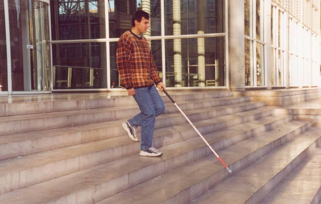 Homme descendant un escalier à l'aide d'une canne longue