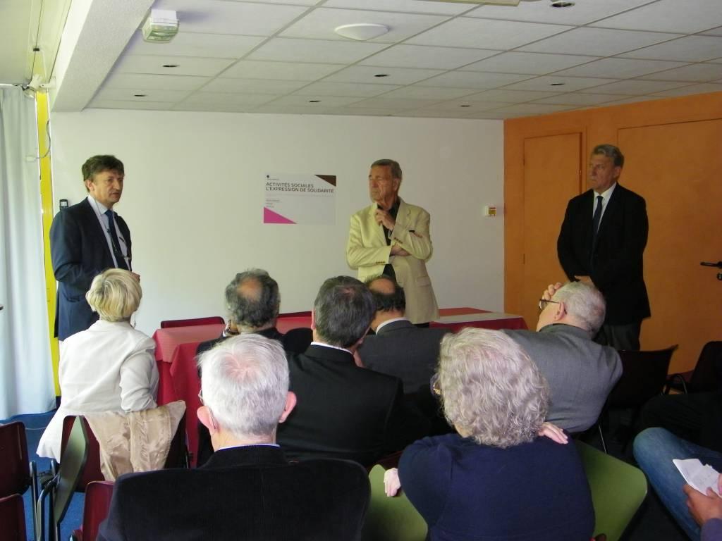 Trois hommes parlant à une assemblée dans une salle de réunion